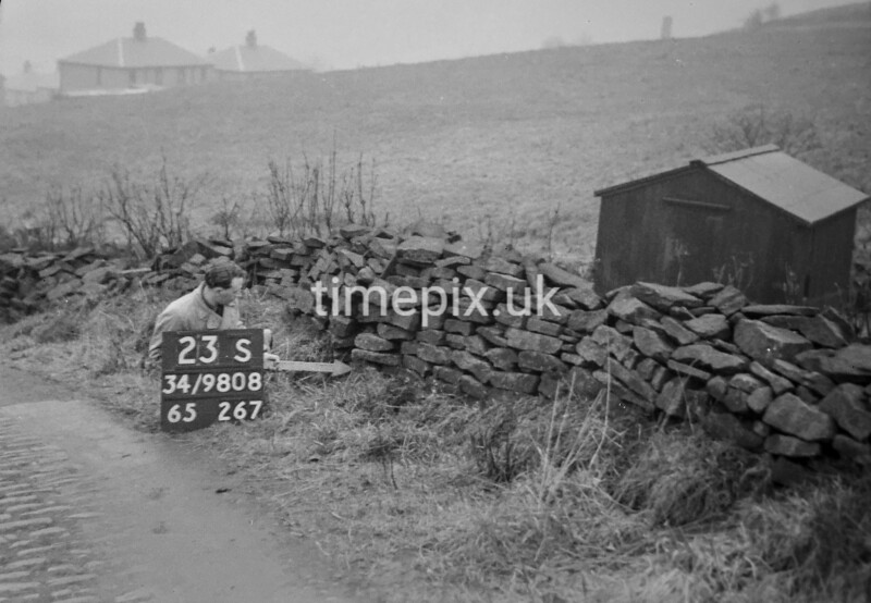 SD980823S, Man marking Ordnance Survey minor control revision point with an arrow in 1950s