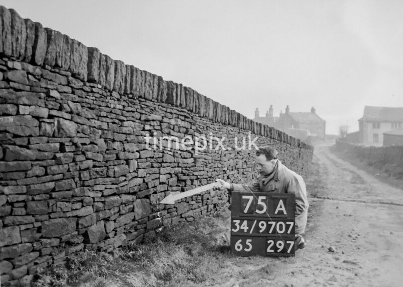 SD970775A, Man marking Ordnance Survey minor control revision point with an arrow in 1950s