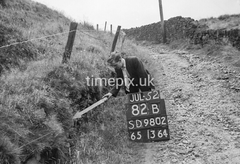 SD980282B, Man marking Ordnance Survey minor control revision point with an arrow in 1950s