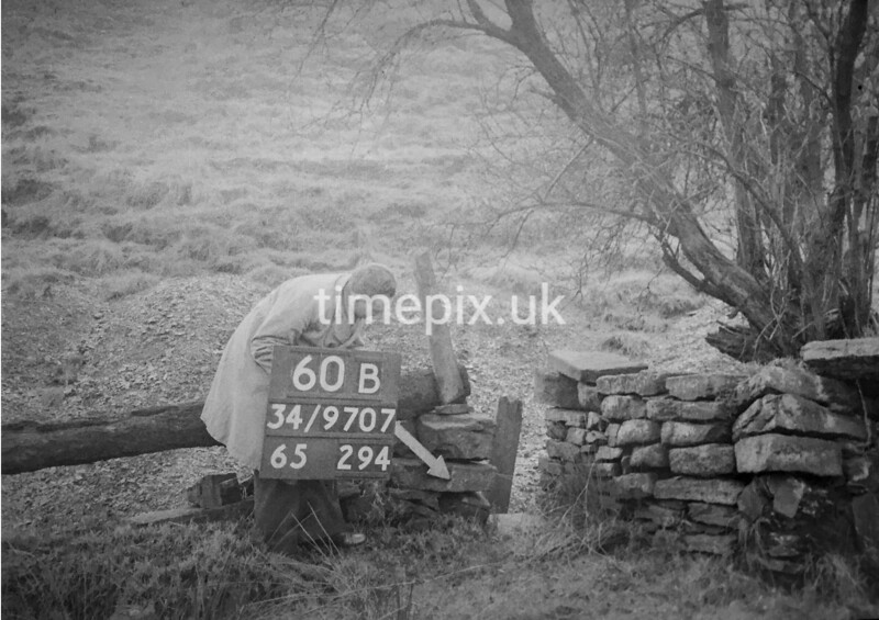 SD970760B, Man marking Ordnance Survey minor control revision point with an arrow in 1950s