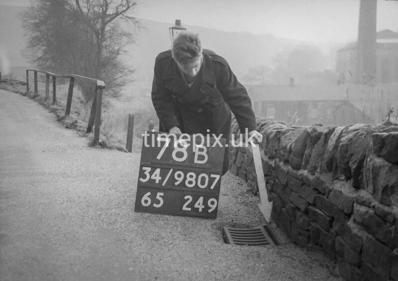 SD980778B, Man marking Ordnance Survey minor control revision point with an arrow in 1950s