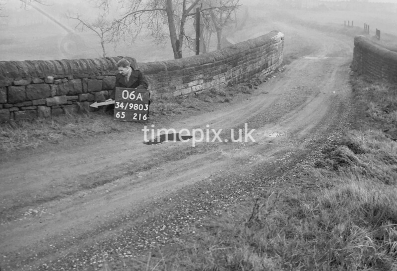 SD980306A, Man marking Ordnance Survey minor control revision point with an arrow in 1950s