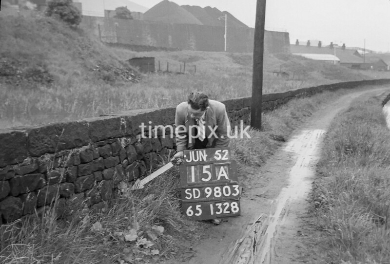 SD980315A, Man marking Ordnance Survey minor control revision point with an arrow in 1950s