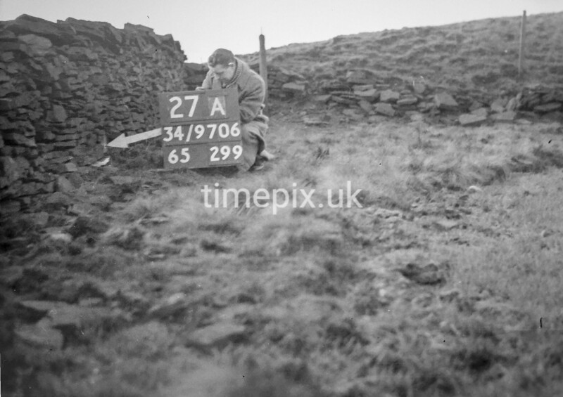 SD970627A, Man marking Ordnance Survey minor control revision point with an arrow in 1950s