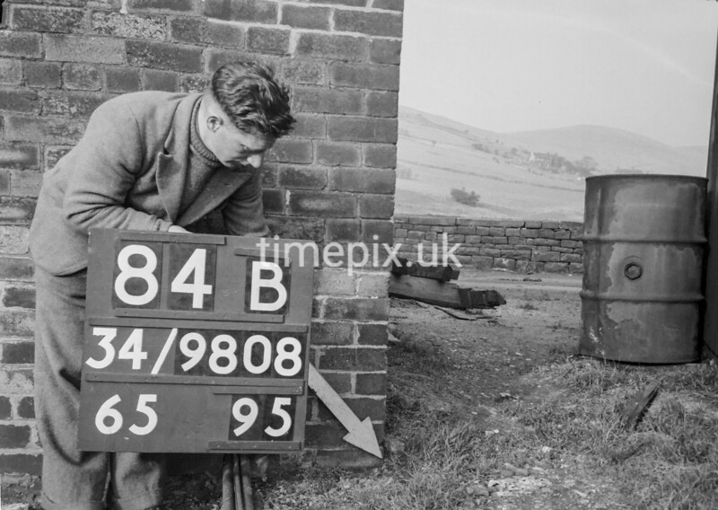 SD980884B1, Man marking Ordnance Survey minor control revision point with an arrow in 1950s