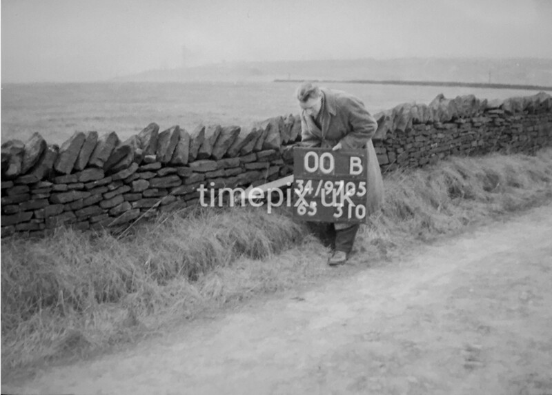 SD970500B, Man marking Ordnance Survey minor control revision point with an arrow in 1950s