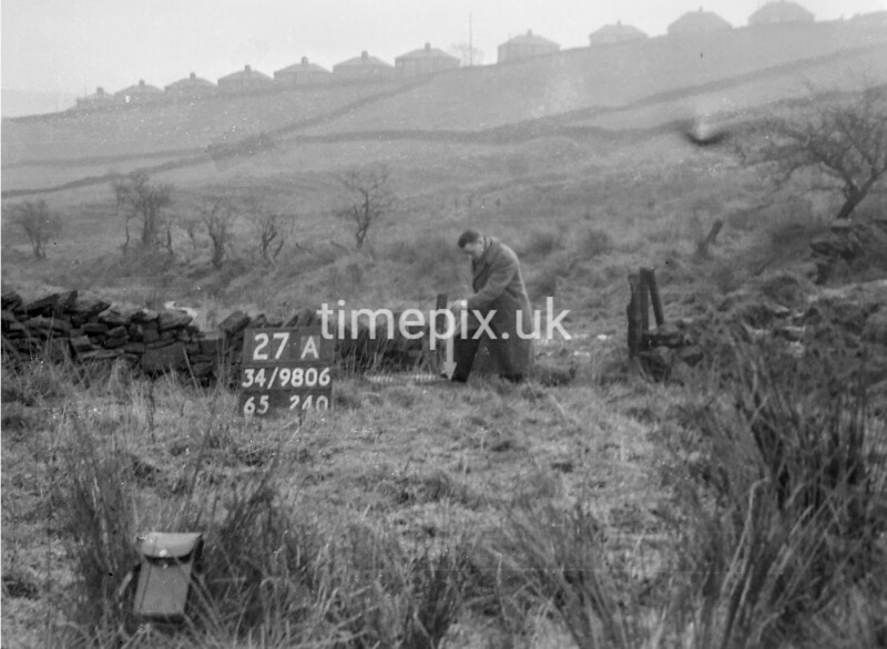 SD980627A, Man marking Ordnance Survey minor control revision point with an arrow in 1950s