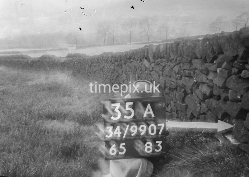 SD990735A, Man marking Ordnance Survey minor control revision point with an arrow in 1950s