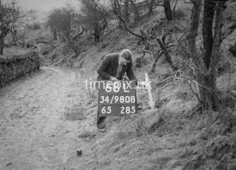 SD980868L, Man marking Ordnance Survey minor control revision point with an arrow in 1950s