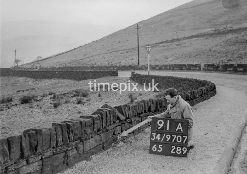 SD970791A, Man marking Ordnance Survey minor control revision point with an arrow in 1950s