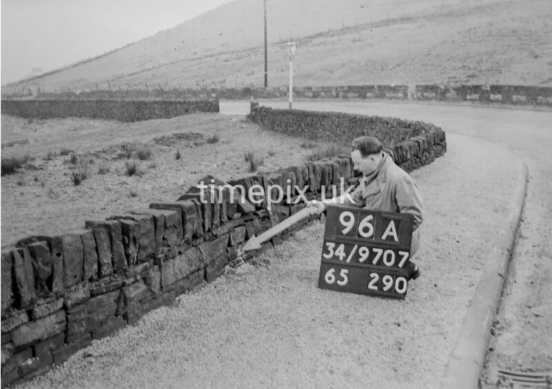 SD970796A, Man marking Ordnance Survey minor control revision point with an arrow in 1950s