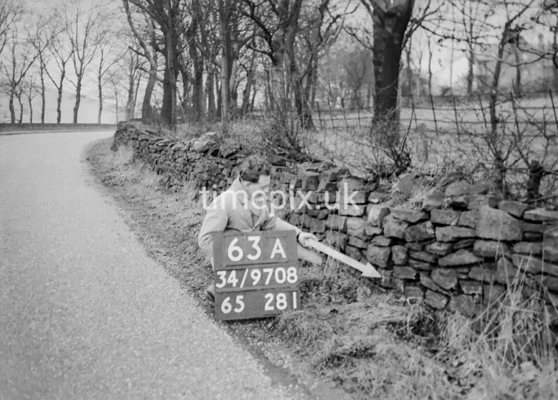 SD970863A, Man marking Ordnance Survey minor control revision point with an arrow in 1950s