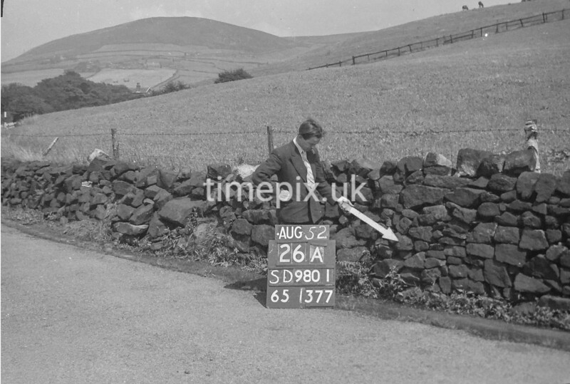 SD980126A, Man marking Ordnance Survey minor control revision point with an arrow in 1950s