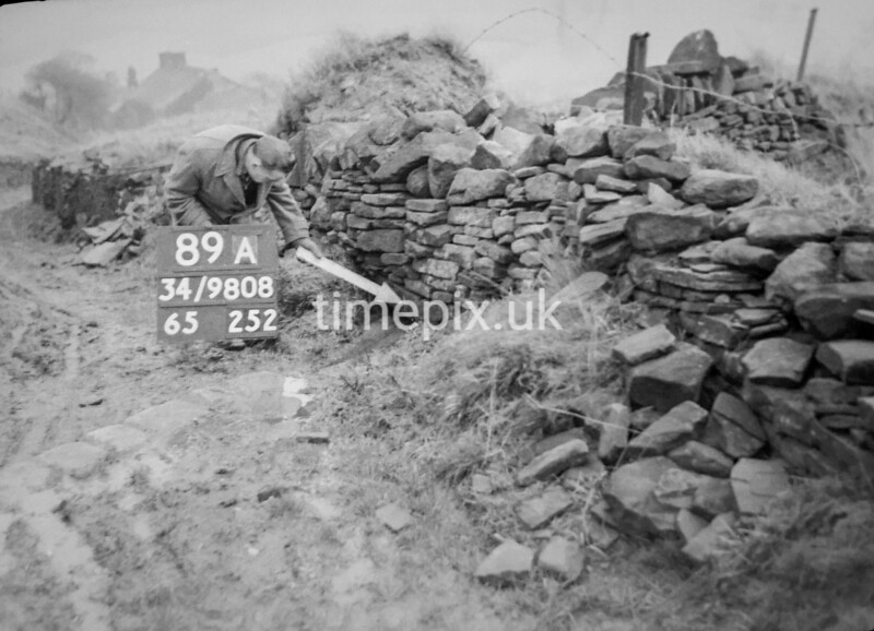 SD980889A, Man marking Ordnance Survey minor control revision point with an arrow in 1950s