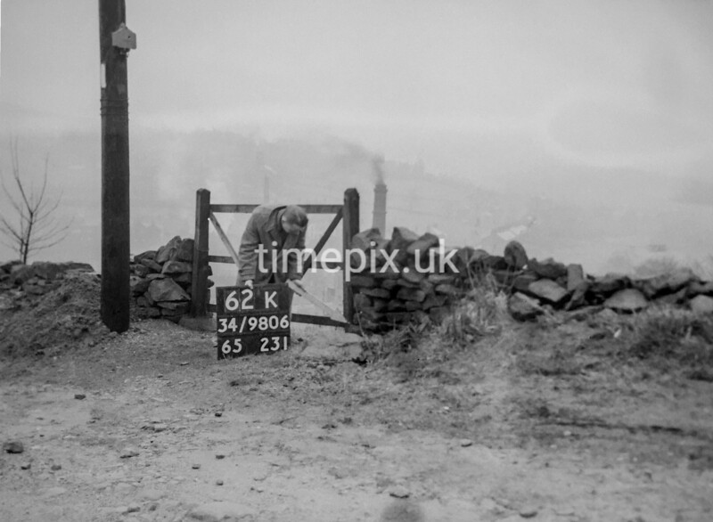 SD980662K, Man marking Ordnance Survey minor control revision point with an arrow in 1950s