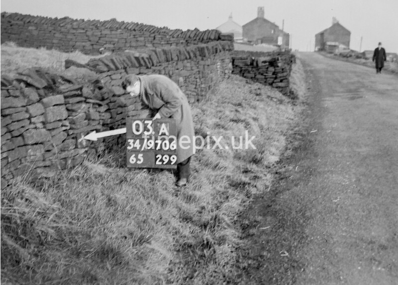 SD970603A, Man marking Ordnance Survey minor control revision point with an arrow in 1950s