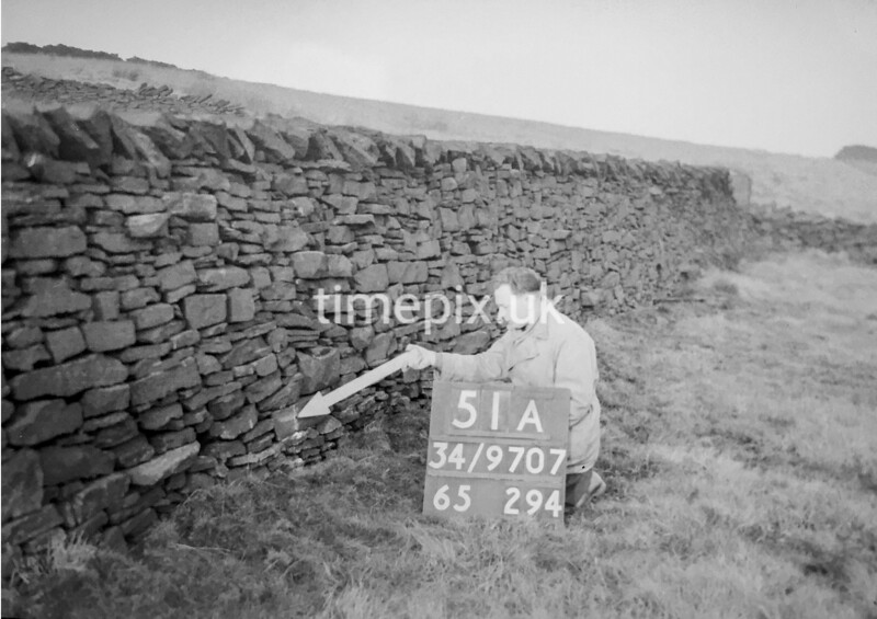 SD970751A, Man marking Ordnance Survey minor control revision point with an arrow in 1950s