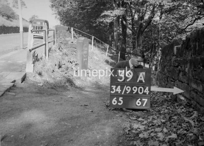 SD990439A, Man marking Ordnance Survey minor control revision point with an arrow in 1950s