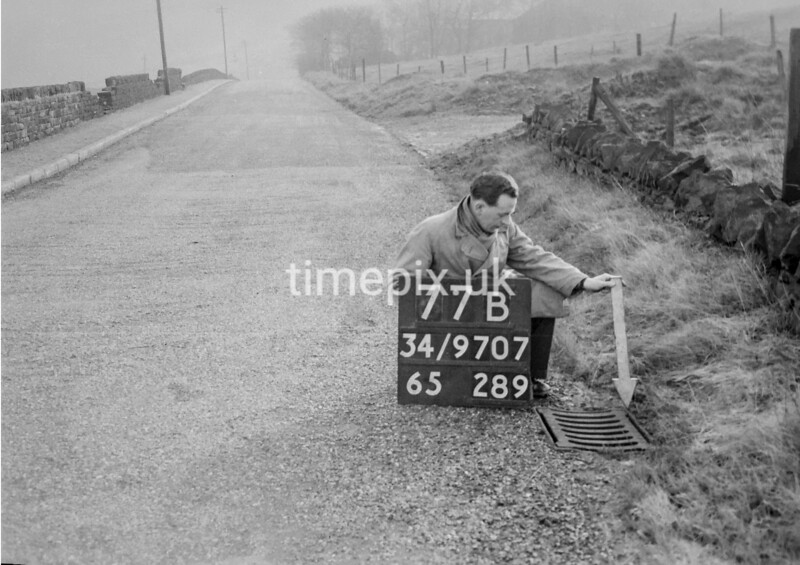 SD970777B, Man marking Ordnance Survey minor control revision point with an arrow in 1950s