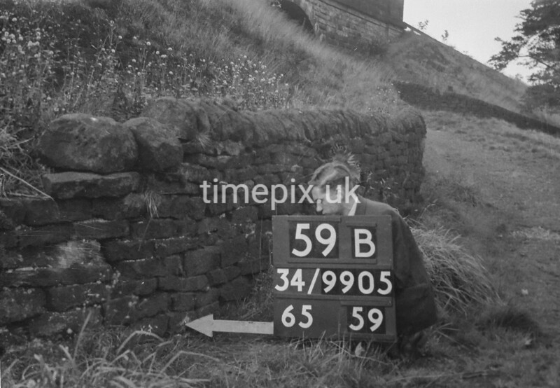 SD990559B, Man marking Ordnance Survey minor control revision point with an arrow in 1950s