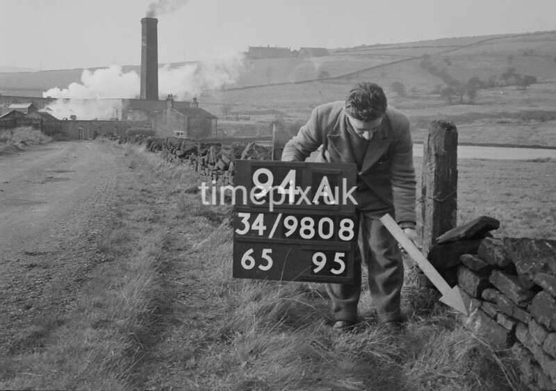 SD980894A, Man marking Ordnance Survey minor control revision point with an arrow in 1950s