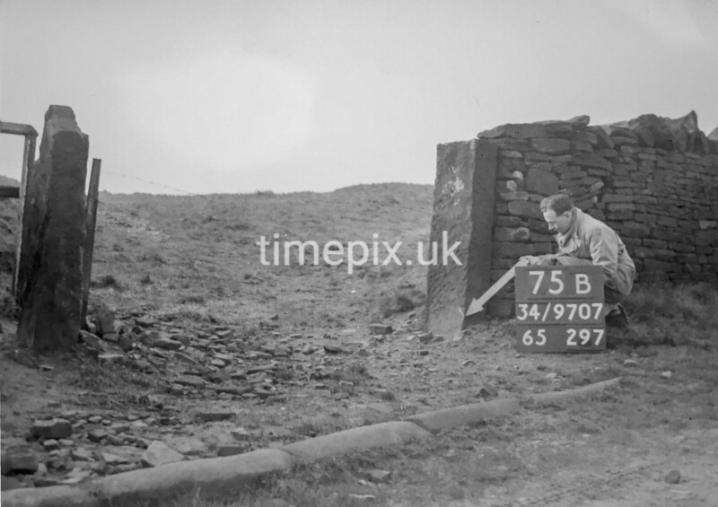 SD970775B, Man marking Ordnance Survey minor control revision point with an arrow in 1950s