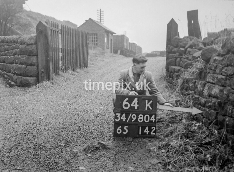 SD980464K, Man marking Ordnance Survey minor control revision point with an arrow in 1950s