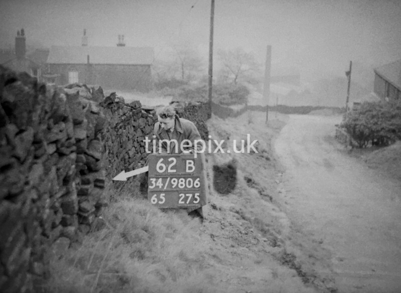 SD980662B, Man marking Ordnance Survey minor control revision point with an arrow in 1950s