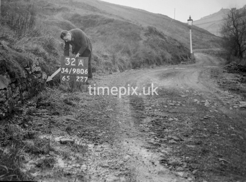 SD980632A, Man marking Ordnance Survey minor control revision point with an arrow in 1950s