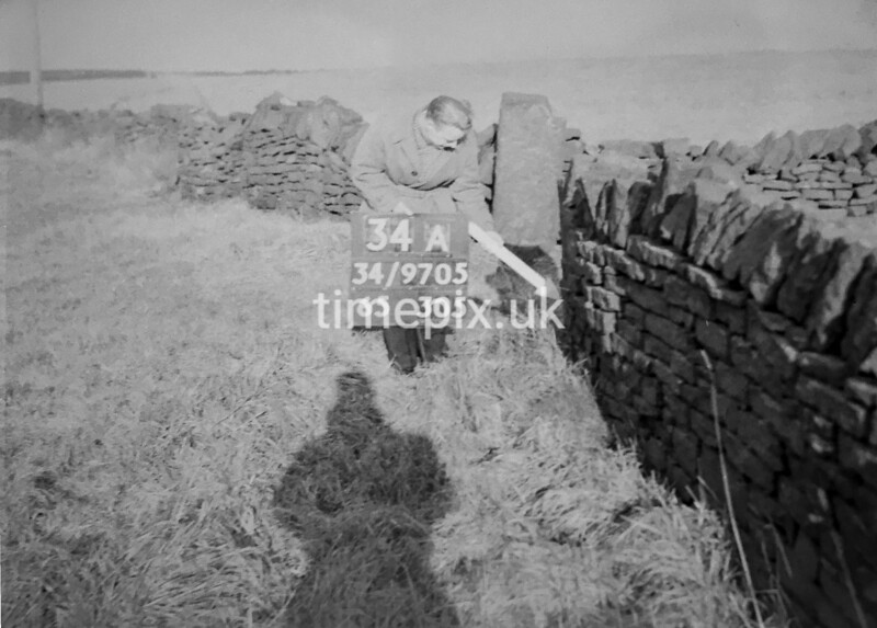 SD970534A, Man marking Ordnance Survey minor control revision point with an arrow in 1950s
