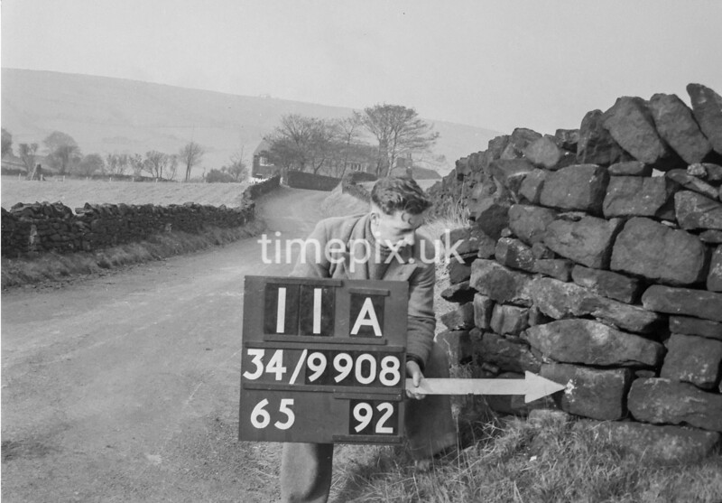 SD990811A, Man marking Ordnance Survey minor control revision point with an arrow in 1950s