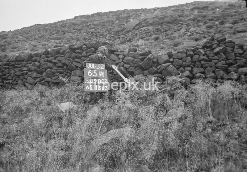 SD980265A, Man marking Ordnance Survey minor control revision point with an arrow in 1950s