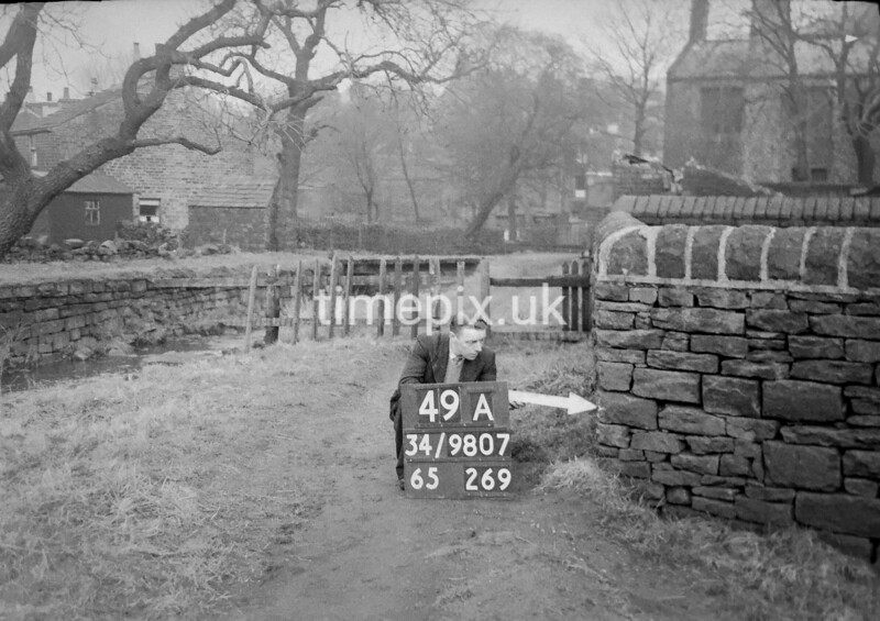 SD980749A, Man marking Ordnance Survey minor control revision point with an arrow in 1950s