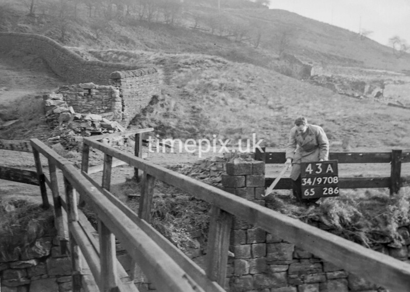 SD970843A, Man marking Ordnance Survey minor control revision point with an arrow in 1950s