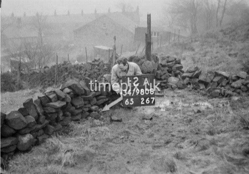 SD980812A, Man marking Ordnance Survey minor control revision point with an arrow in 1950s