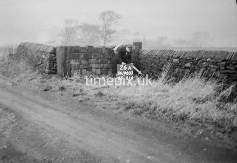 SD980326A, Man marking Ordnance Survey minor control revision point with an arrow in 1950s