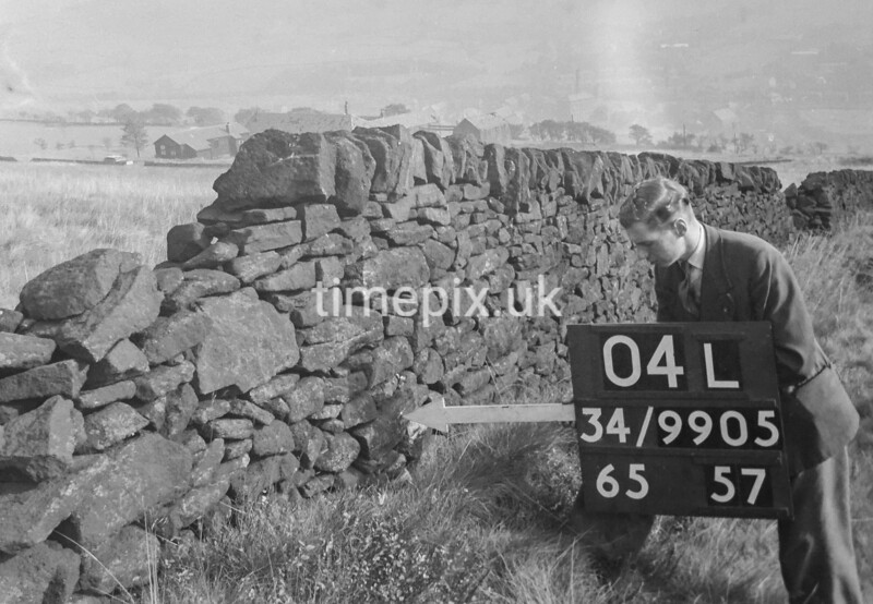 SD990504L2, Man marking Ordnance Survey minor control revision point with an arrow in 1950s
