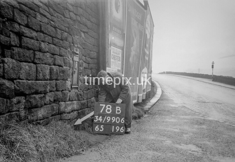 SD990678B1, Man marking Ordnance Survey minor control revision point with an arrow in 1950s