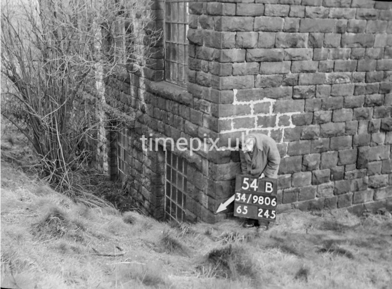 SD980654B, Man marking Ordnance Survey minor control revision point with an arrow in 1950s