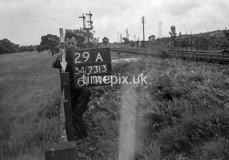 SD731329A, Man marking Ordnance Survey minor control revision point with an arrow in 1940s