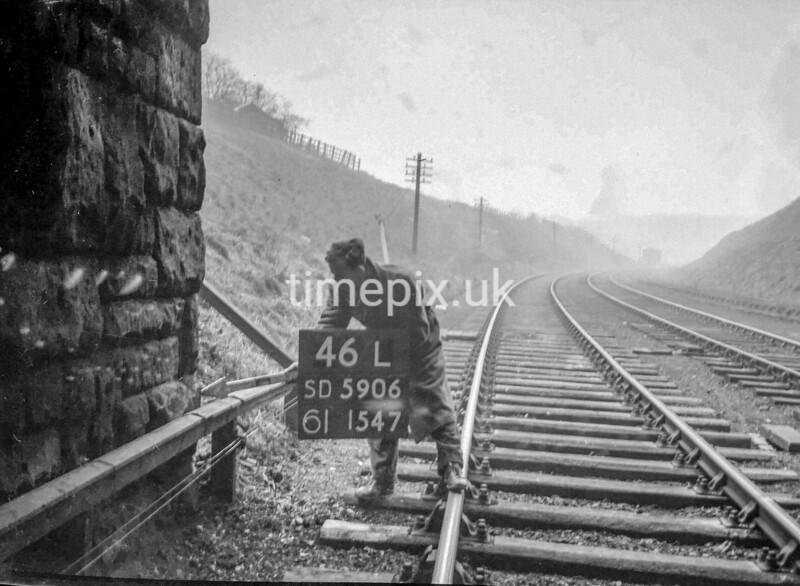 SD590646L, Man marking Ordnance Survey minor control revision point with an arrow in 1950s