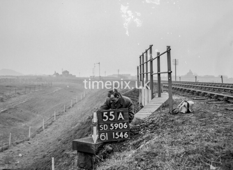 SD590655A, Man marking Ordnance Survey minor control revision point with an arrow in 1950s