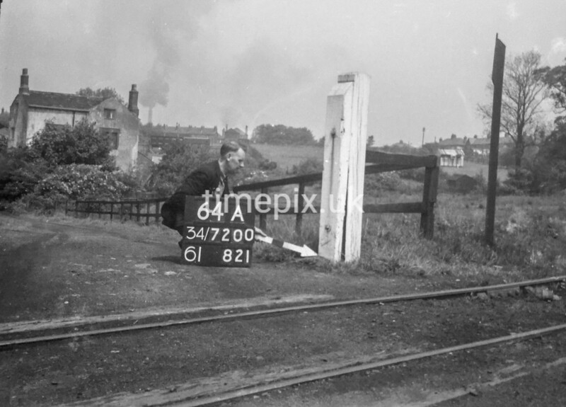 SD720064A, Man marking Ordnance Survey minor control revision point with an arrow in 1950s