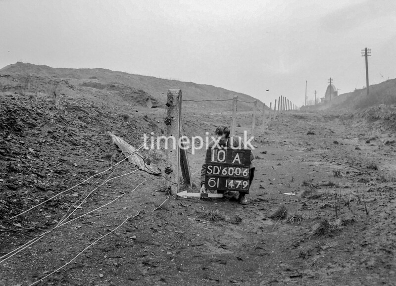 SD600610A, Man marking Ordnance Survey minor control revision point with an arrow in 1950s