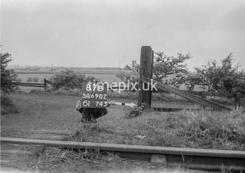 SD690287B, Man marking Ordnance Survey minor control revision point with an arrow in 1950s