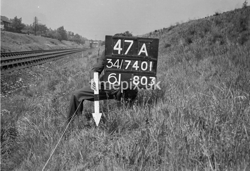 SD740147A, Man marking Ordnance Survey minor control revision point with an arrow in 1940s