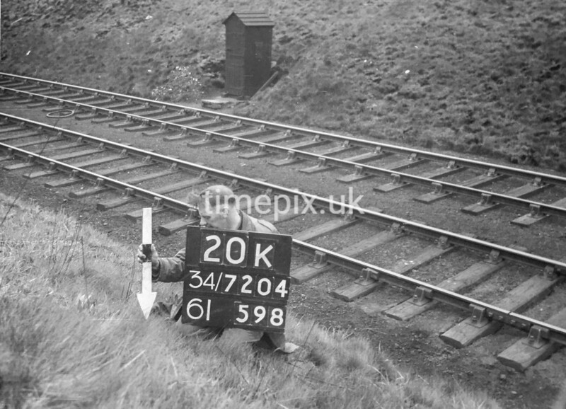 SD720420K, Man marking Ordnance Survey minor control revision point with an arrow in 1950s