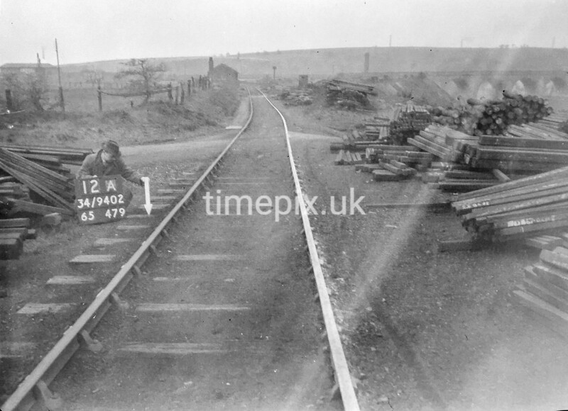 SD940212A, Man marking Ordnance Survey minor control revision point with an arrow in 1950s
