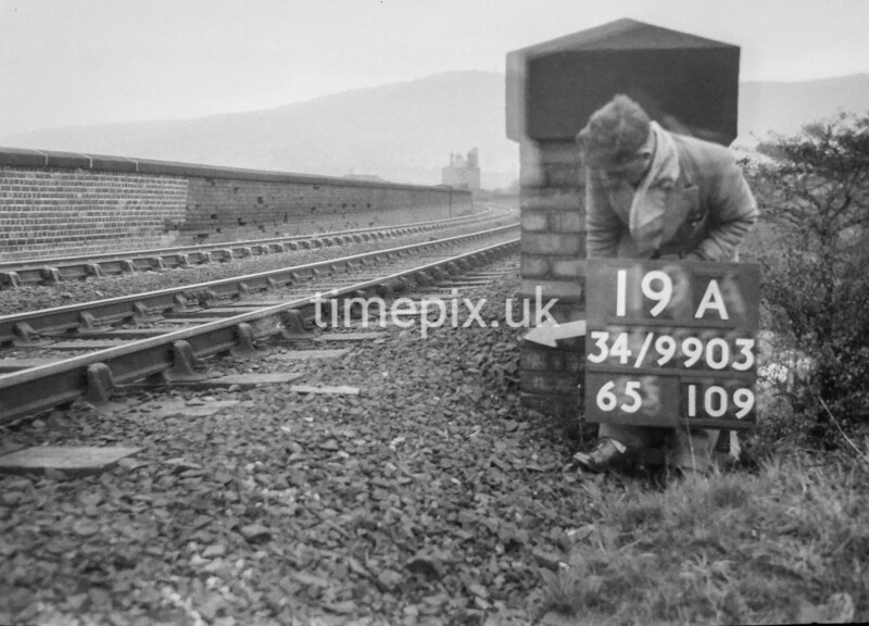 SD990319A, Man marking Ordnance Survey minor control revision point with an arrow in 1950s