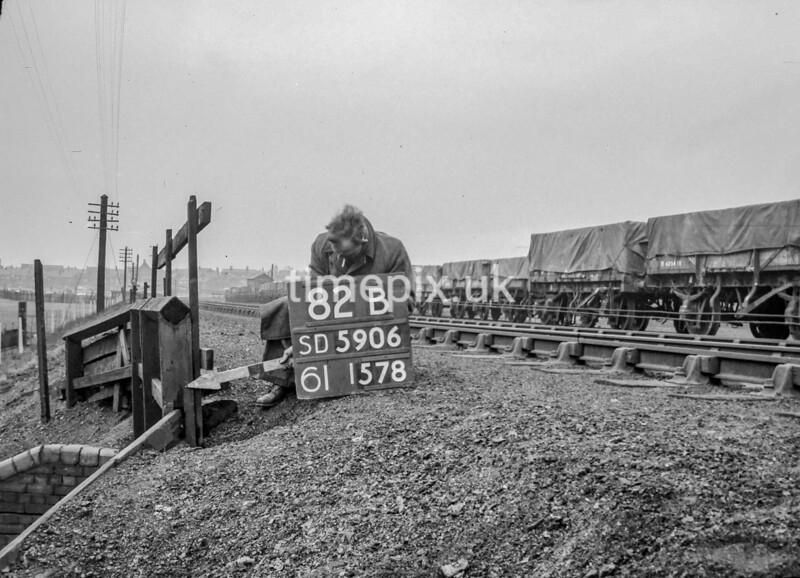 SD590682B, Man marking Ordnance Survey minor control revision point with an arrow in 1950s